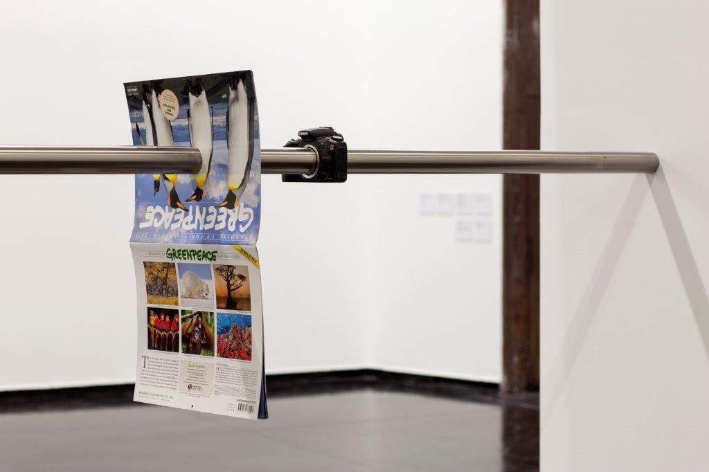 img_Richard Frater, *April*, 2015/17, Installation view, modified Greenpeace Standing up for the Earth calendar, waterjet cut Canon camera body, stainless steel tube, Canon EF 300mm f/2.8L, Courtesy Richard Frater